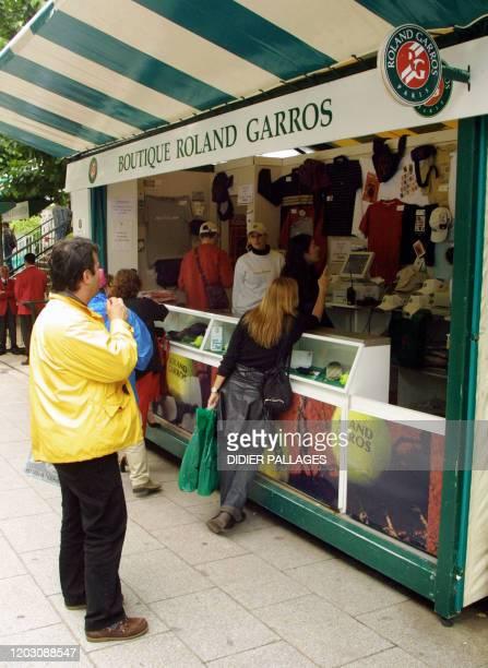 Des visiteurs regardent, en juin 2002 à Paris, des produits dérivés vendus dans une boutique en marge du tournoi de tennis de Roland Garros. AFP...