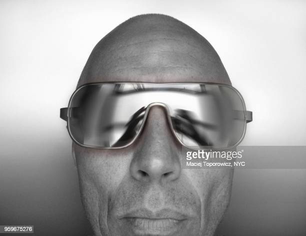 Desaturated headshot of a man in silver mirror sunglasses.