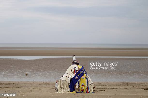 A descendant of Comanche indian soldiers prays on Utah Beach on June 9 2014 in SainteMarieduMont northwestern France 14 Comanche code talkers landed...