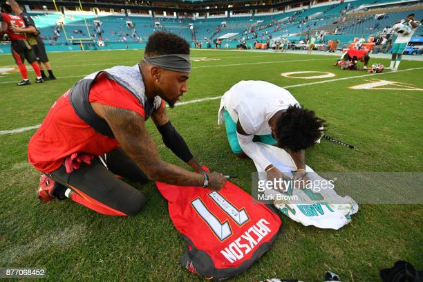 DeSean Jackson of the Tampa Bay Buccaneers and Jarvis Landry of the Miami Dolphins exchange and sign uniforms after the game at Hard Rock Stadium on...