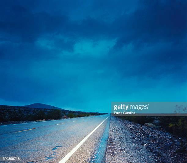 desert highway at dusk - ominous stock photos and pictures