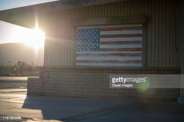 desert home with american flag painting at sunset - small town stock pictures, royalty-free photos & images