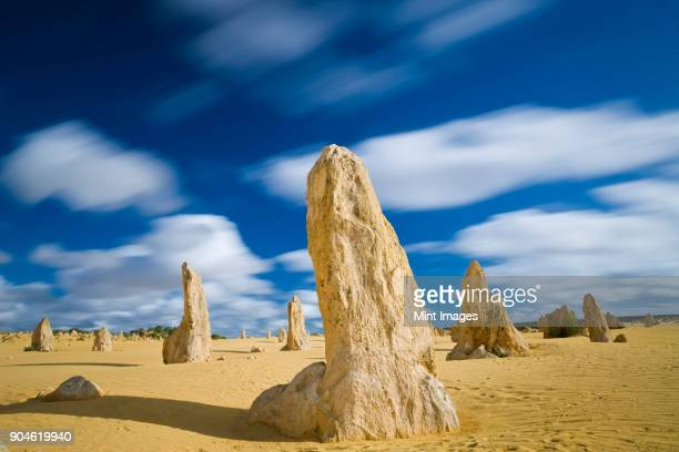 Desert landscape dotted with limestone pinnacles under a cloudy sky.