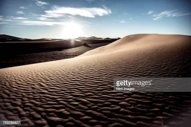 Desert landscape with sand dunes under a cloudy sky.