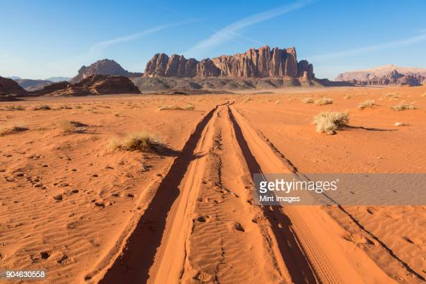 desert landscape with tire tracks leading to distant mountain. - river bed stock photos and pictures