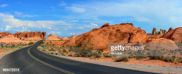 desert road and red rocks - southern usa stock photos and pictures