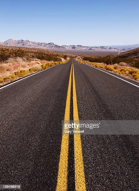 desert road leading into the distance - double yellow line stock photos and pictures