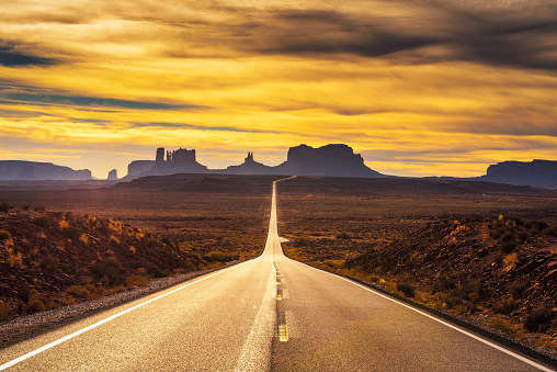 Desert road leading to Monument Valley at sunset 919792788