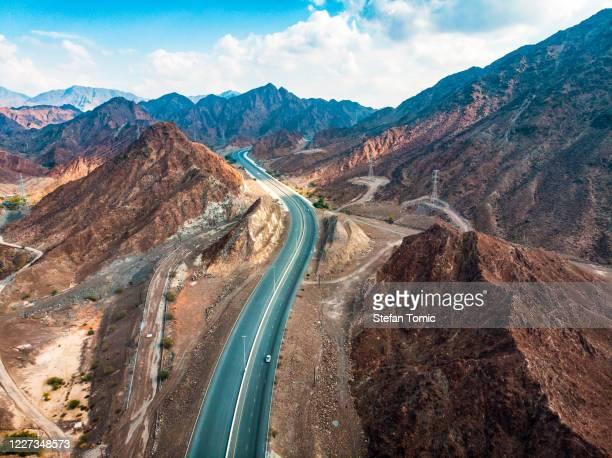 carretera del desierto a través de la cordillera de hajar que se extiende a través de los eau - oman fotografías e imágenes de stock