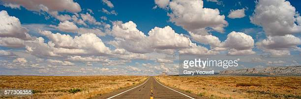Desert road with cloud formations above