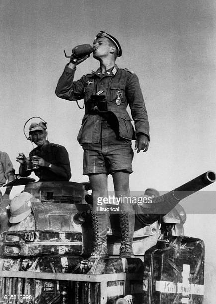 A desert soldier of Germany's Afrika Korps stands atop a tank and takes a long refreshing drink