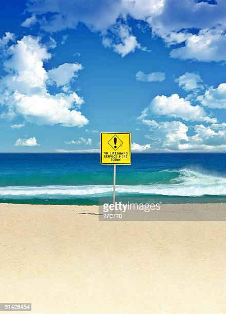 Deserted Australian surf beach with dramatic clouds and Danger sign