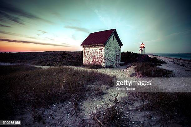 a deserted beach building and brant point lighthouse on nantucket island - robb reece stock-fotos und bilder