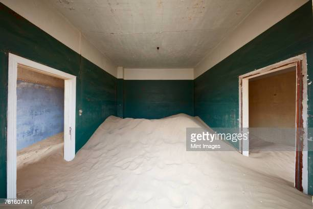 A deserted building, a room with painted walls and two doorways, and a heap of sand engulfing half the room.
