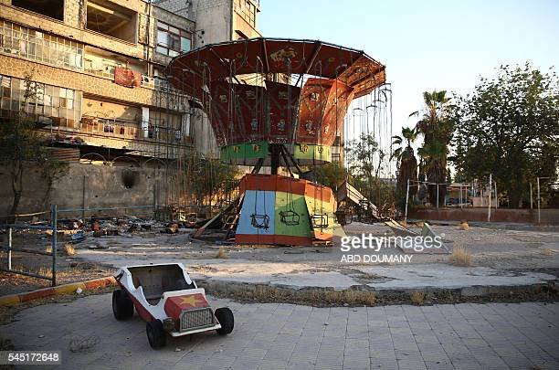 A deserted children's carousel is seen in the rebelheld town of Douma east of the capital Damascus on the first day of the Eid alFitr holiday which...