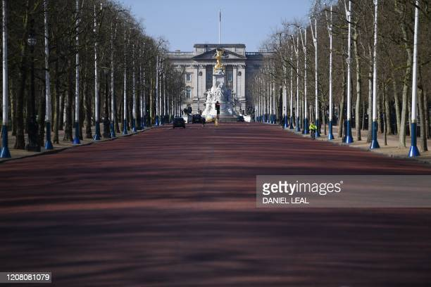 A deserted Mall leading to Buckingham Palace is pictured in London on the morning on March 24 2020 after Britain ordered a lockdown to slow the...