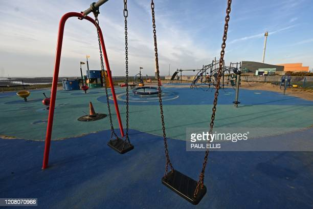 A deserted playground is pictured in Rhyl north Wales on March 23 2020 Prime Minister Boris Johnson warned on Sunday he may impose tougher controls...