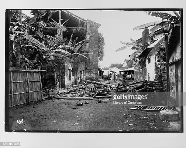 Deserted street in ruined village during the Philippine Insurrection, an uprising in response to America's colonization of the area following the...