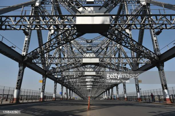 A deserted view of the iconic Howrah Bridge that spans the Hooghly River on day 3 of the threeweek nationwide lockdown to check the spread of...