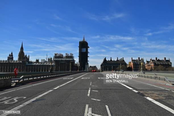 Deserted Westminster Bridge is pictured looking north around Monday lunch time, in central London, March 23 as governments scramble to defend their...