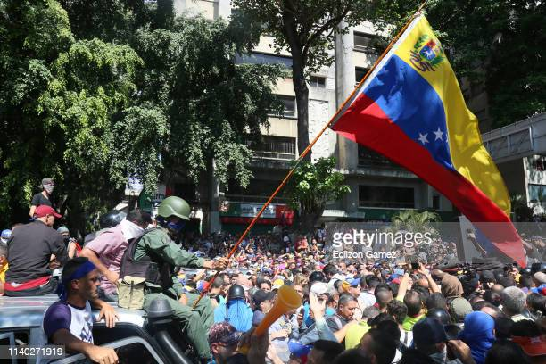 A deserter military officer who joined supporters of Juan Guaido waves a Venezuelan flag at Plaza Altamira on April 30 2019 in Caracas Venezuela...