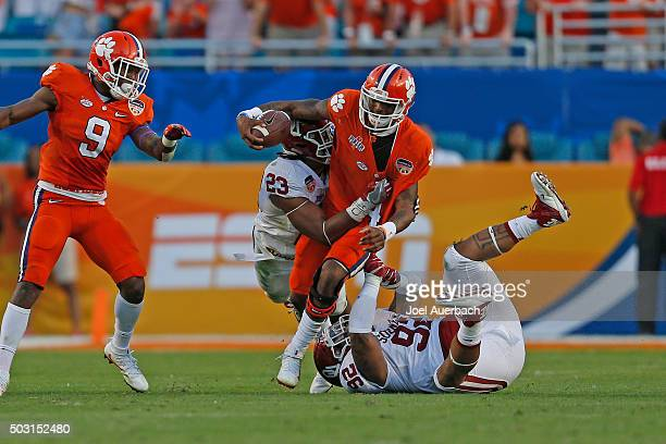 Deshaun Watson of the Clemson Tigers is tackled by Matthew Romar and Devante Bond of the Oklahoma Sooners during the 2015 Capital One Orange Bowl at...