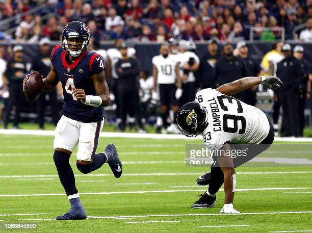 Deshaun Watson of the Houston Texans avoids a tackle attempt by Calais Campbell of the Jacksonville Jaguars during the fourth quarter at NRG Stadium...