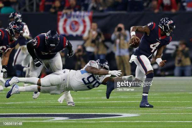 Deshaun Watson of the Houston Texans escapes the tackle by Jurrell Casey of the Tennessee Titans in the third quarter at NRG Stadium on November 26,...