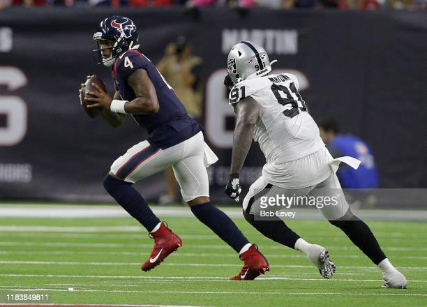 Deshaun Watson of the Houston Texans is chased out of the pocket by Benson Mayowa of the Oakland Raiders during the fourth quarter at NRG Stadium on...