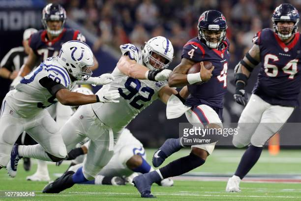 Deshaun Watson of the Houston Texans is forced to scramble under pressure by Margus Hunt of the Indianapolis Colts and Anthony Walker in the third...