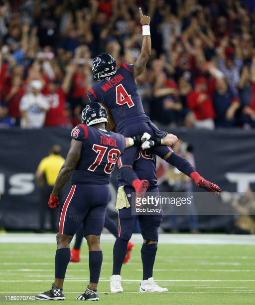 Deshaun Watson of the Houston Texans is hoisted by Nick Martin and Laremy Tunsil after throwing a touchdown pass to DeAndre Hopkins during the fourth...