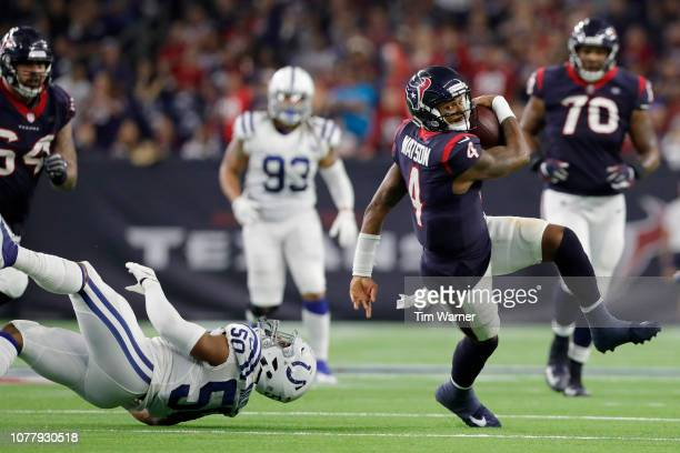 Deshaun Watson of the Houston Texans is tripped up by Anthony Walker of the Indianapolis Colts in the third quarter during the Wild Card Round at NRG...