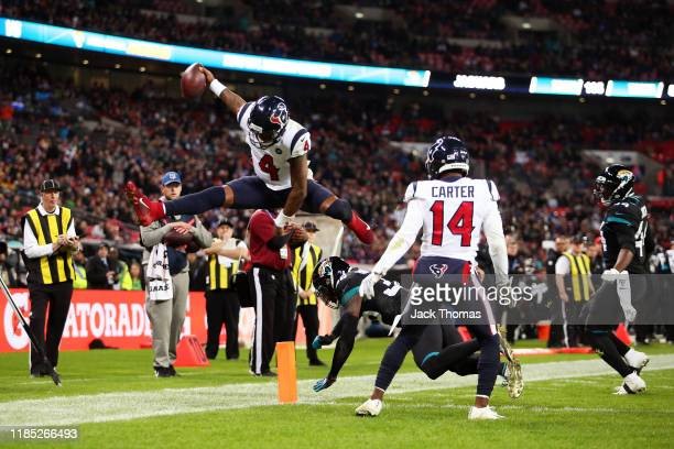Deshaun Watson of the Houston Texans jumps over Ronnie Harrison of the Jacksonville Jaguars for a touchdown was is later disallowed after review...