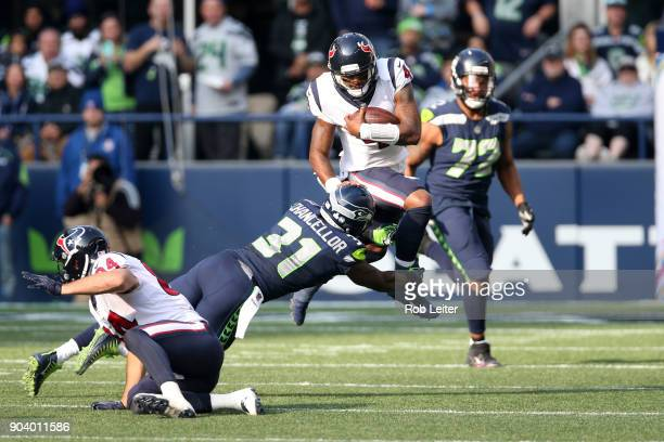 Deshaun Watson of the Houston Texans leaps over Kam Chancellor during the game against the Seattle Seahawks at CenturyLink Field on October 29 2017...