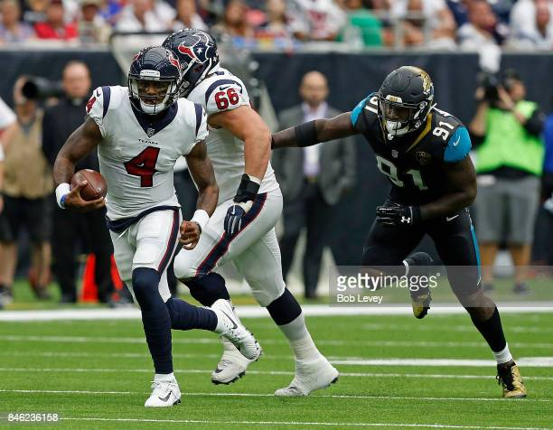 Deshaun Watson of the Houston Texans runs out of the pocket as Nick Martin attempts to keep Yannick Ngakoue of the Jacksonville Jaguars from tackling...