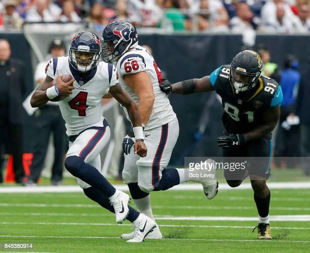 Deshaun Watson of the Houston Texans runs with the ball as Nick Martin blocks Yannick Ngakoue of the Jacksonville Jaguars at NRG Stadium on September...