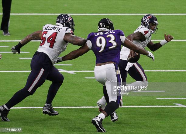 Deshaun Watson of the Houston Texans rushes away from Calais Campbell of the Baltimore Ravens as Senio Kelemete attempts to slow him down at NRG...