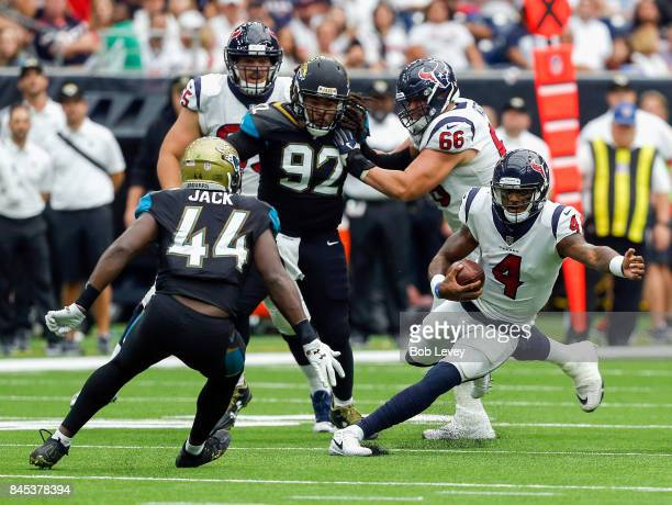 Deshaun Watson of the Houston Texans rushes with the ball as Myles Jack of the Jacksonville Jaguars and Eli Ankou in the fourth quarter at NRG...