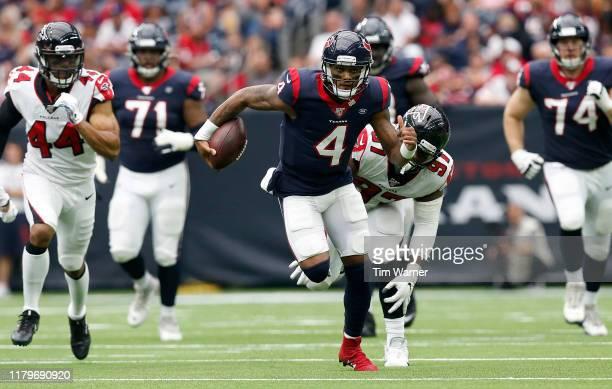 Deshaun Watson of the Houston Texans scrambles past Grady Jarrett of the Atlanta Falcons in the first half at NRG Stadium on October 6, 2019 in...