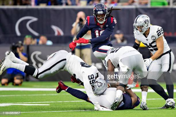 Deshaun Watson of the Houston Texans slides to the ground and is hit by Arden Key of the Oakland Raiders at NRG Stadium on October 27 2019 in Houston...
