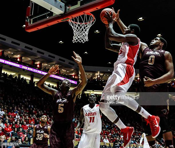Deshawn Delaney of the New Mexico Lobos jumps to shoot as Marvin Williams and teammate Jamaal Samuel of the LouisianaMonroe Warhawks defends during...