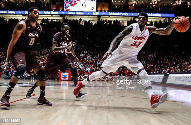 Deshawn Delaney of the New Mexico Lobos saves the ball from going out as Marvin Williams and Tylor Ongwae of the LouisianaMonroe Warhawks follow...