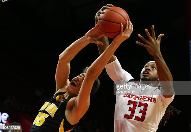 Deshawn Freeman of the Rutgers Scarlet Knights pulls a rebound away from Luka Garza of the Iowa Hawkeyes during the first half of a game at Rutgers...