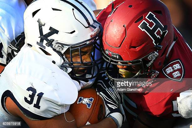 Deshawn Salter of the Yale Bulldogs is tackled by Jordan Hill of the Harvard Crimson in the first quarter of a game at Harvard Stadium on November 19...
