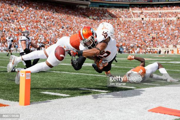 DeShon Elliott of the Texas Longhorns hits Chris Lacy of the Oklahoma State Cowboys at the goal line forcing a fumble in the fourth quarter at...