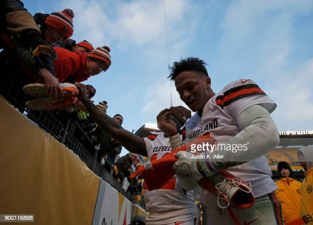 DeShone Kizer of the Cleveland Browns autographs his cleats to give them to a fan at the conclusion of the Pittsburgh Steelers 2824 win over the...