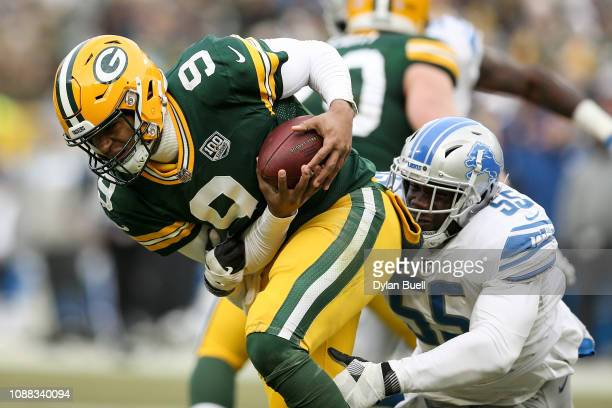 DeShone Kizer of the Green Bay Packers avoids a sack attempt by Eric Lee of the Detroit Lions in the fourth quarter at Lambeau Field on December 30...