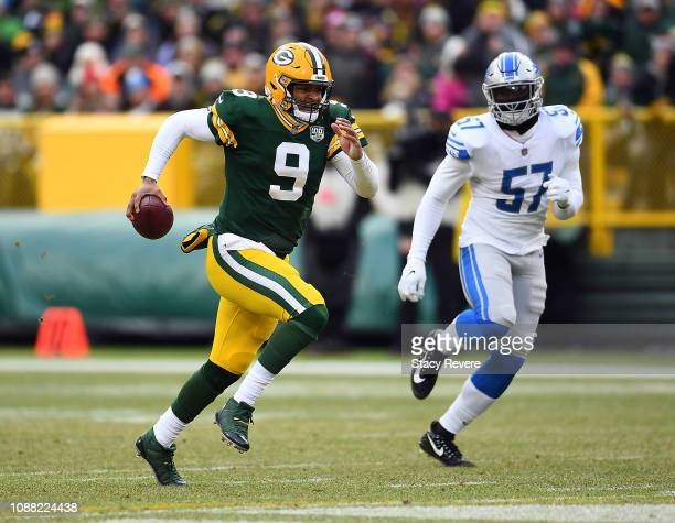 DeShone Kizer of the Green Bay Packers runs in front of Eli Harold of the Detroit Lions during the second half of a game at Lambeau Field on December...