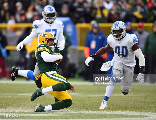 DeShone Kizer of the Green Bay Packers slides in front of Jarrad Davis of the Detroit Lions during the second half of a game at Lambeau Field on...