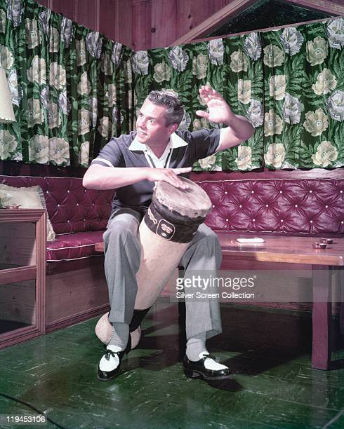 Desi Arnaz , Cuban-born US musician and actor, beating a conga drum with his hand in a publicity still issued for the US television series, 'I Love...